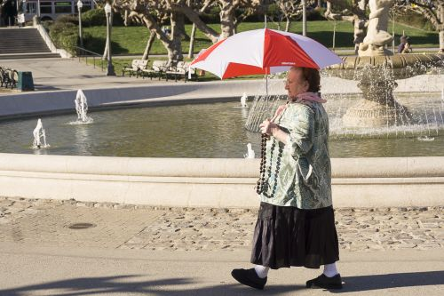 Old woman walking by a fountain