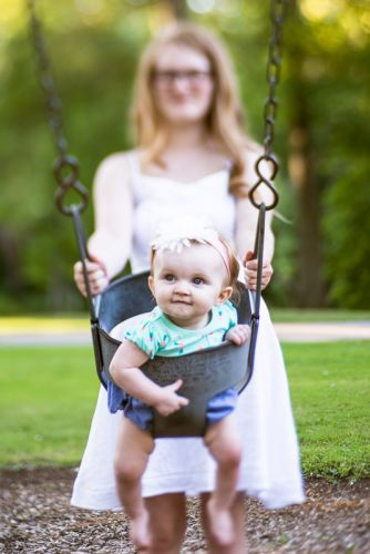 Mother and daughter playing on a swing